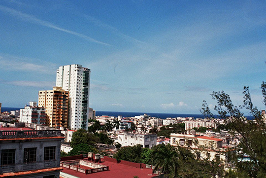 Rooftops and buildings leading to the ocean.
