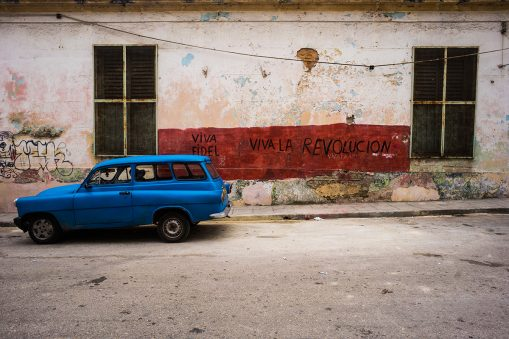 "Blue car in front of a building on which ""viva fidel"" and ""viva la revolucion"" are painted"