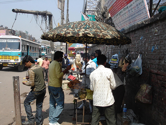 People grouped around an outdoor food stall, marked by a camouflage umbrella.