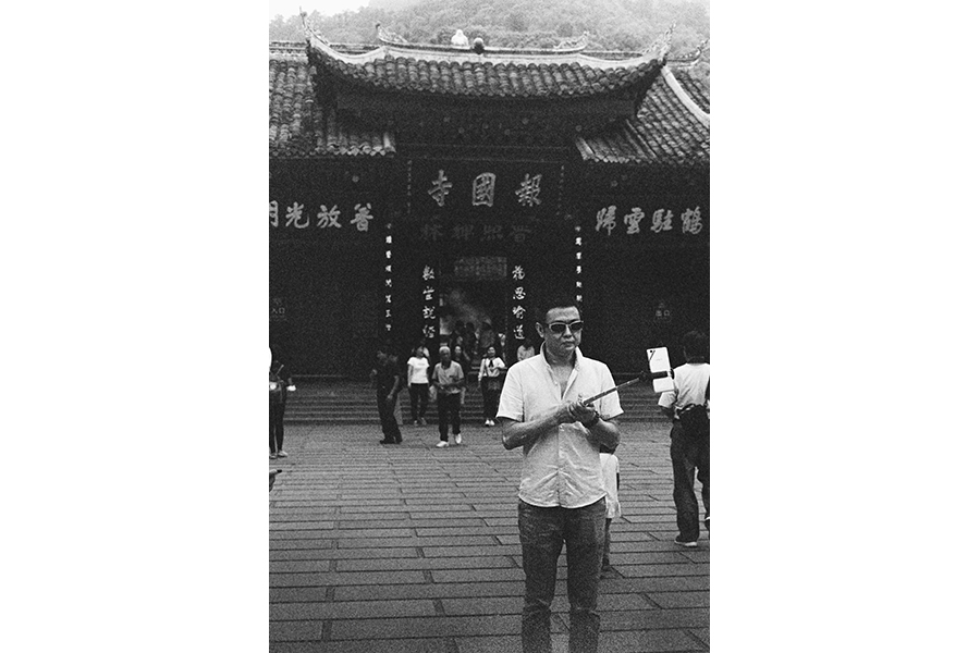 Black and white photograph of a man in sunglasses and a short-sleeve white button-down using a selfie-stick to take a selfie in front of the entrance to a temple