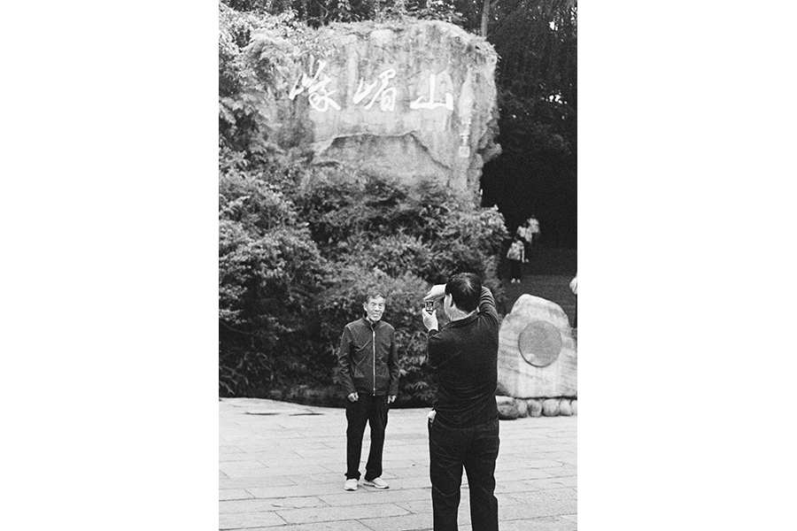 Black-and-white photograph of two men, one takes a photo of the other, his image visible in his phone screen; the subject stands in front of a rock with an inscription and plants