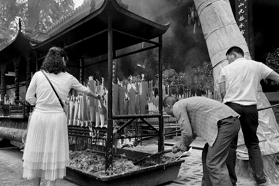 Black and white photograph of a woman, seen from the back, lighting a candle in a covered display of large candles; near the right edge of the photo two men rake the wax drippings that have collected below