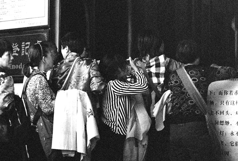 Black-and-white photograph of a line of people; the image is close-up enough that the line eclipses features of the background
