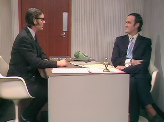 """Two men in suits sitting across from each other at a small desk (""""Monty Python"""" still)."""