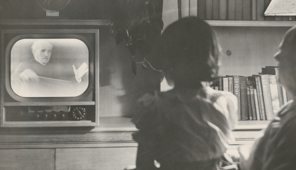 Black and white photo of a young girl watching television