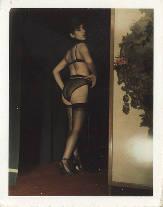 A Polaroid of a woman—standing with her back to us, body and head turned towards us—posing in her lingerie. Photograph taken in Carlo Mollino's villa in Turin.
