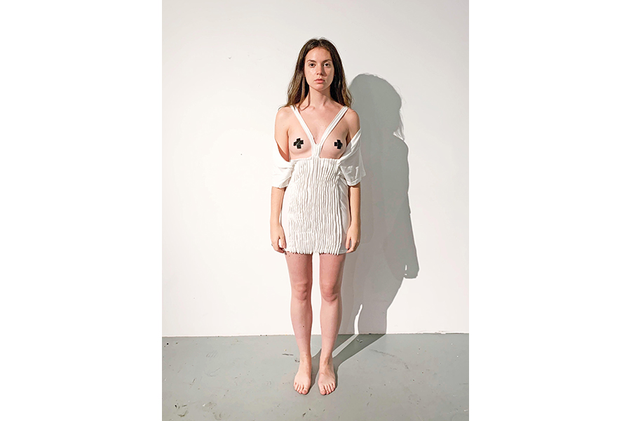 1-	A model stands against a white wall wearing a white garment. The sleeves have been cut so that the fabric forms a Y-shaped yoke around the models neck. At mid-chest, the base of the yoke meets the rest of the fabric, which forms a straight line across the torso and continuing in cuff sleeves around the model's elbows. The fabric from torso to mid-thigh has been sewn into many vertical pleats. An X of black tape covers the model's nipples.