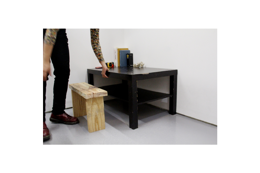 A light colored stool, and black coffee table with a vertebra model and small stack of books.