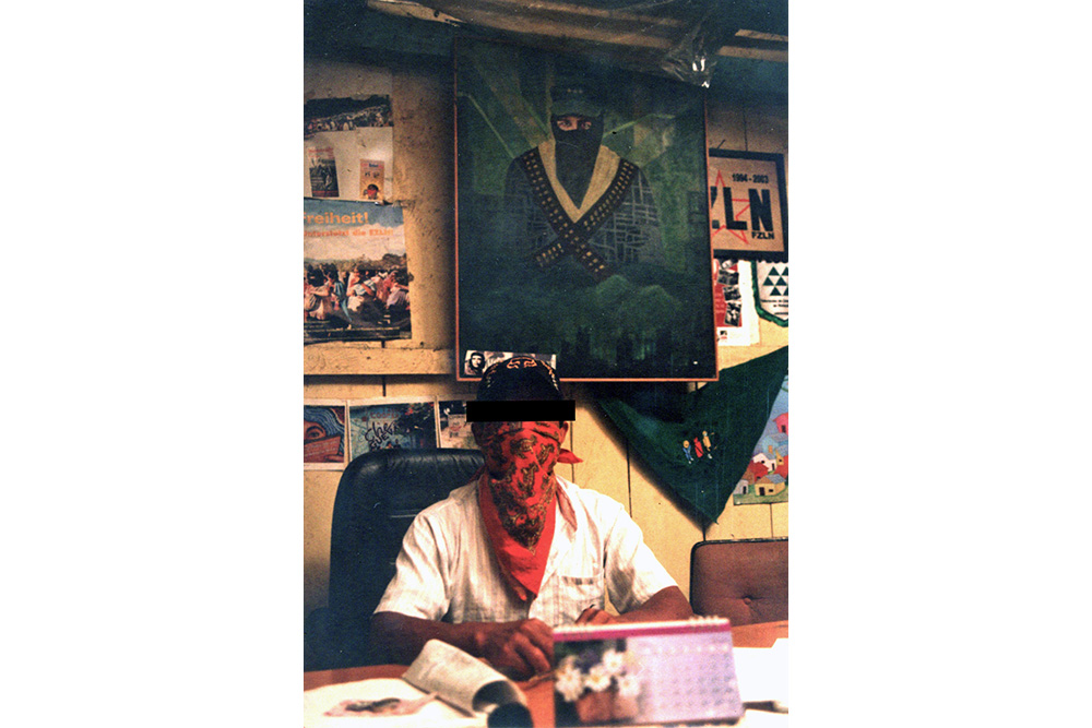 A man, wearing a bandana over his face, seated at a desk in front of a portrait of a Zapatistas.