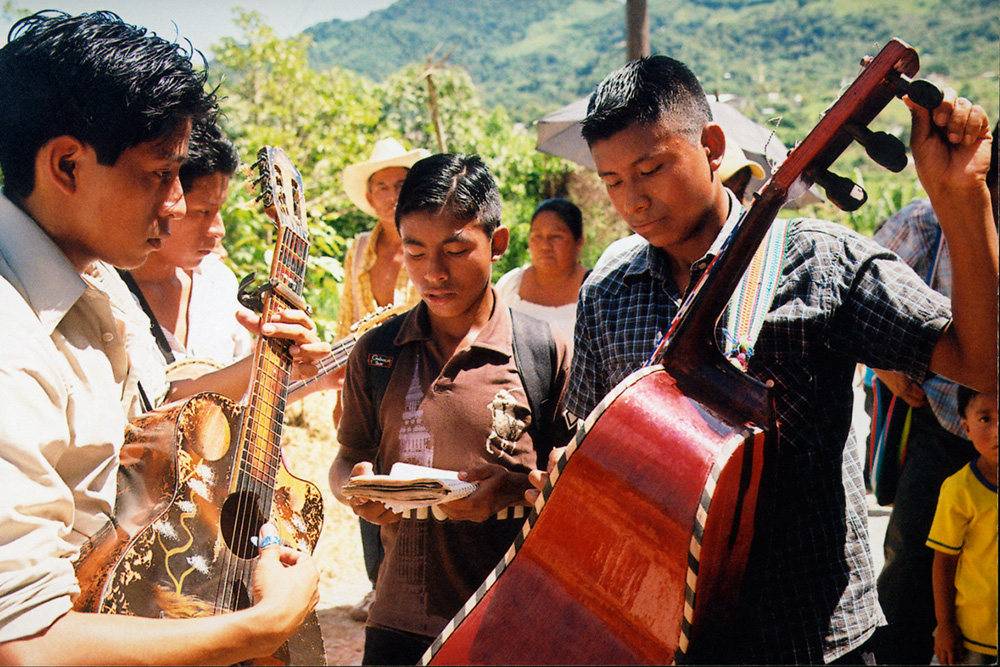 A group of Chiapan men holding guitars (and one holding a notebook) huddled; some onlookers.