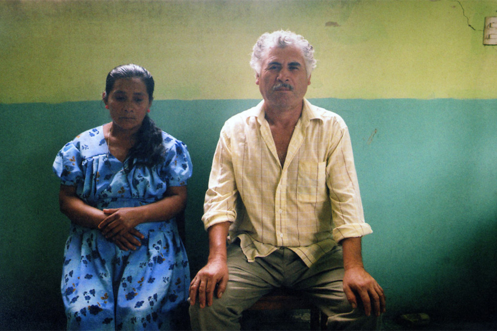 An older Chiapan man and woman, against a blue and yellow wall, gazing toward the camera.
