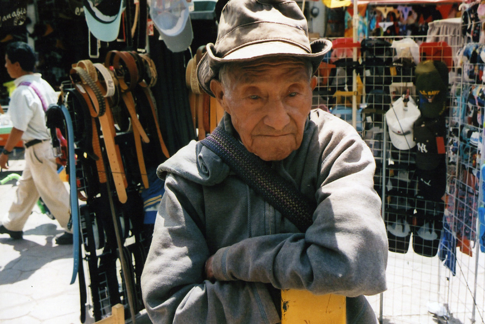 An older Mexican man wearing a hat, stood in front of a stall selling belts and hats.