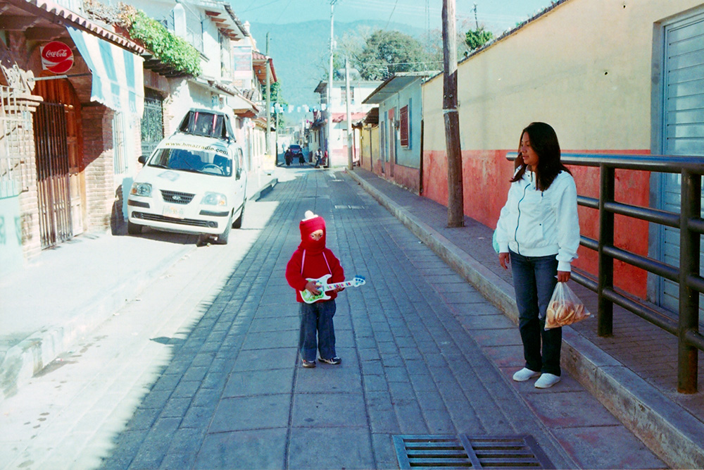 A young kid in a small alleyway wearing a red sweatshirt; his mother watching him from a curb.