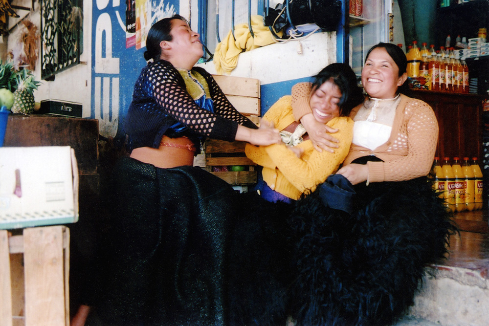 Three Chiapan women, laughing and holding each other.