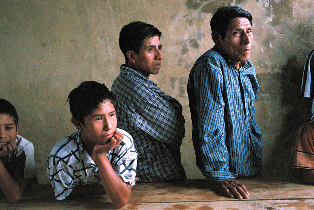 A Chiapan man of three generations, stood behind a table against a neutral wall, gazing at something off-camera.