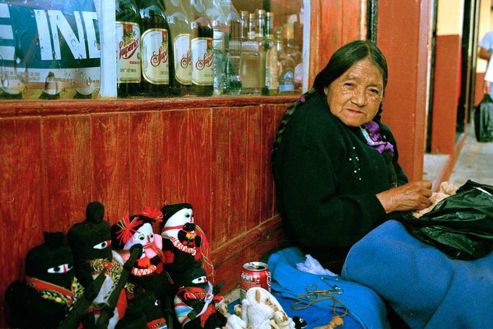 An older Chiapan woman gazing to the camera, sitting on a bench with two pairs of handmade dolls and a coke can.