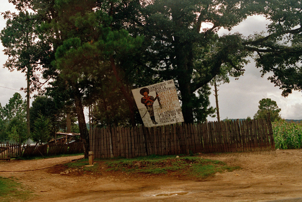 A Zapatista poster on a tree behind a fence.