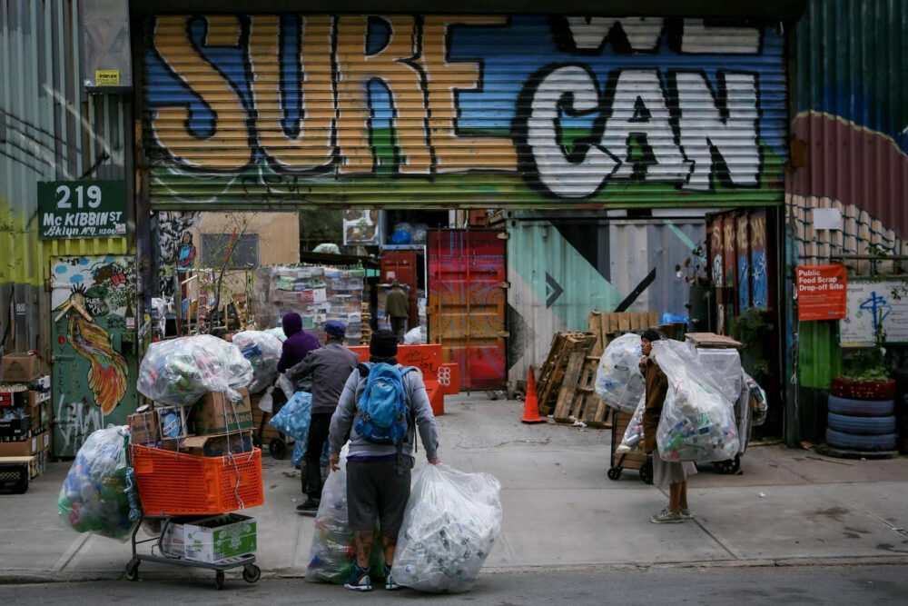 Entrance to Sure We Can: people carry bags of aluminum cans into the facility; a colorful mural on the partially rolled-up garage grate reads Sure We Can