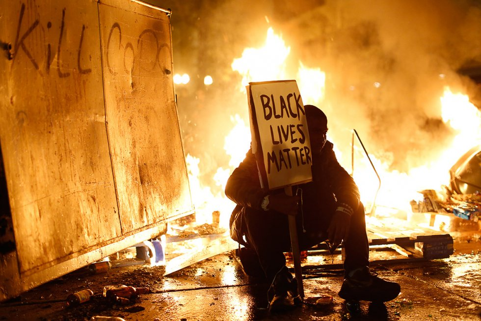 "A protester kneeling with a Black Lives Matter sign, in front of fire and next to a board with ""kill cops"" graffiti."