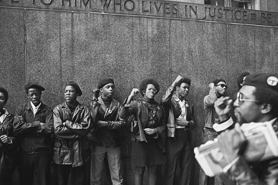 A group of black men in berets—Black Panthers—lined up in front of a courthouse, some with their fists up.