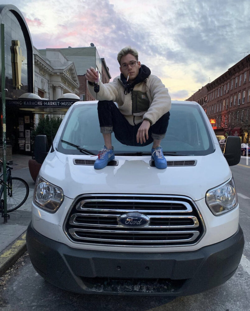 Pictured, Iz crouched confidently, lit cigarette in mouth keys in hand, on the hood of a white Ford tour van.