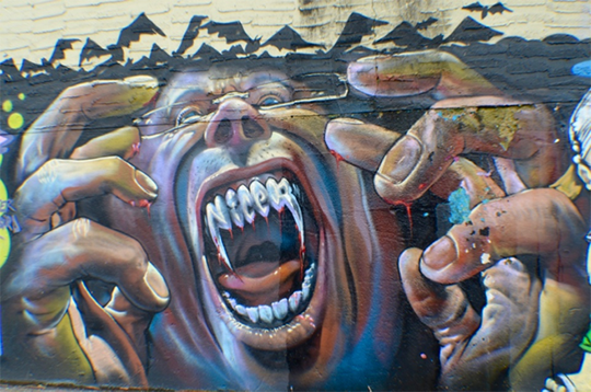 Photograph of graffiti mural depicting a screaming face with vampire teeth, and fleshy hands raised in a claw-like gesture, bats rising in silhouette in background