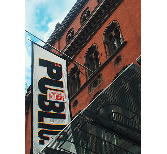 "Photograph of the facade of The Public Theater in Manhattan, a banner that says ""THE PUBLIC"" and ""RADICALLY INCLUSIVE"" on prominent display."