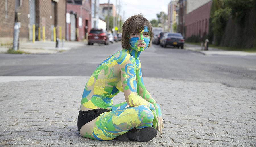 A person with blue, green and yellow body paint sits in the center of a stone street and gazes into the camera.