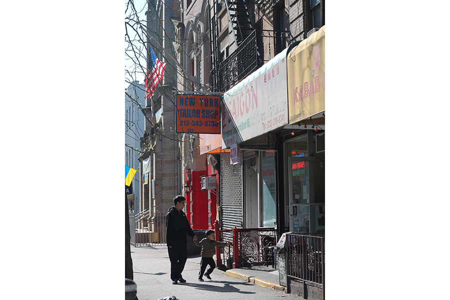 A city street showing a row of mixed-use walk-ups; a young child leads a man into a storefront with a white awning