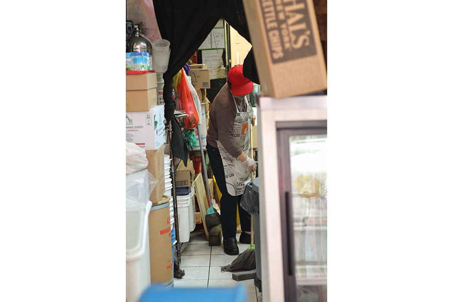 View into a storeroom crowded by boxes; someone in a baseball cap and apron mops the narrow space in between