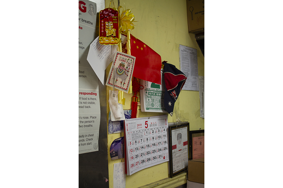 A bulletin board and yellow wall crowded with posters, cards, a calendar, and a small flag