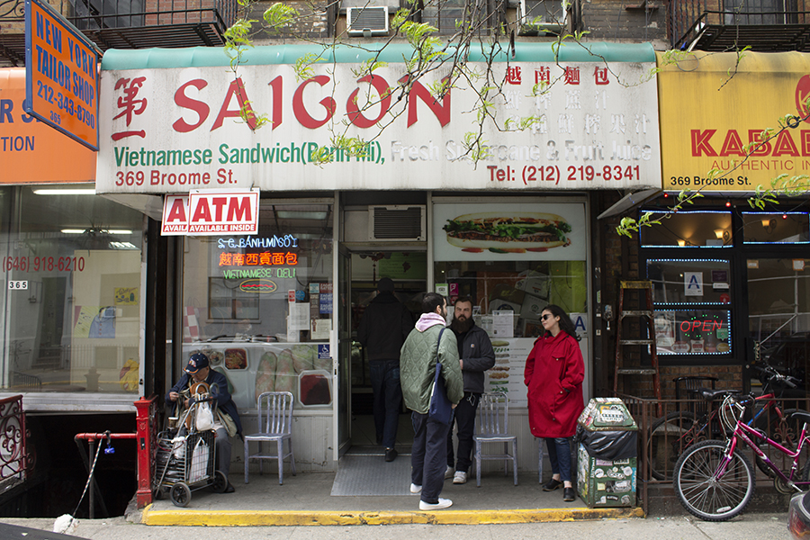 Saigon Vietnamese Sandwich Deli as seen from the street. One customer sits in a metal chair to the left of the entrance; to the right of the entrance, three people stand chatting