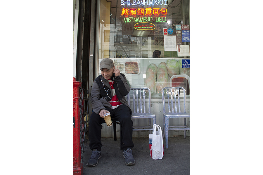 A man wearings a baseball cap and earbuds sits in one of the metal chairs outside Saigon Vietnamese Sandwich Deli, a paper cup in hand