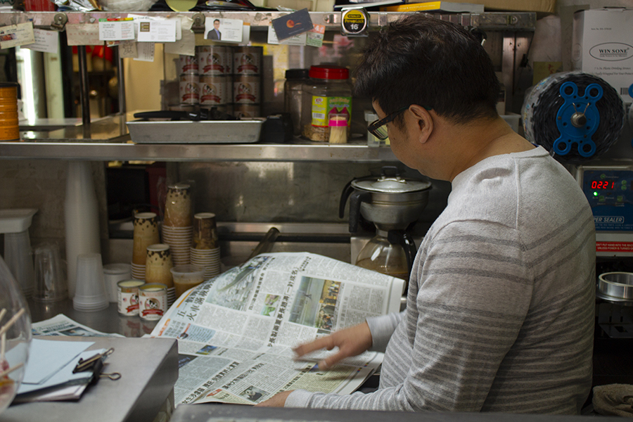 A man, seen from the side, reads the paper standing at the deli's kitchen counter