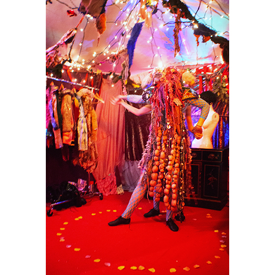 Two figures in mask and beaded costume stand back-to-back, holding hands outstretched and each with one foot in tendue, in a circle of rosepetals on a red carpet, in a tent with sting lighting; in the background are a costume rack and a mannequin bust form