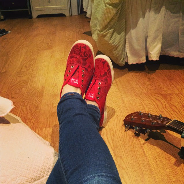 Crossed legs on a wood floor, clad in denim and red sneakers; the neck of a guitar is visible at the right edge of the frame.