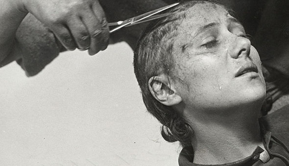 Joan of Arc, head tilted back, getting her hair trimmed.