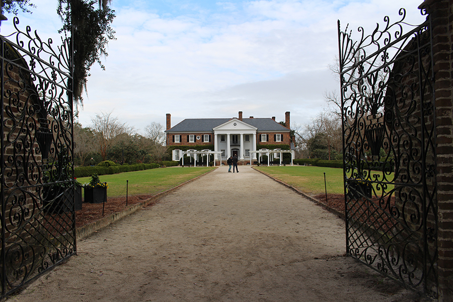 The Boone Hall big house: a stately brick structure nestled behind swirling iron gates and flanked by a rose garden.