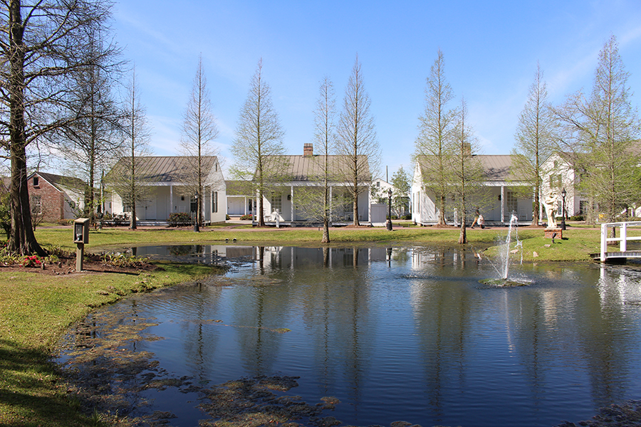 Beyond a glassy pond with a fountain in its center sits a row of identical white guest cottages. Like typical slave huts, each house has two windows, two doors, a simple front porch, wooden panels, and a tin roof.