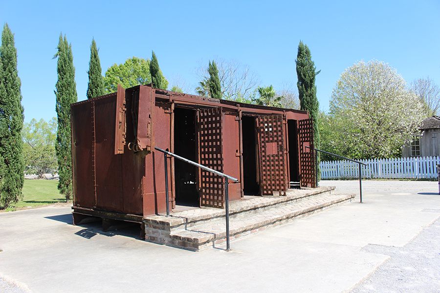 The three lattice doors of a rusty metal cage are open, revealing the windowless cells awaiting within. The box looks more like a container for cargo or livestock than humans