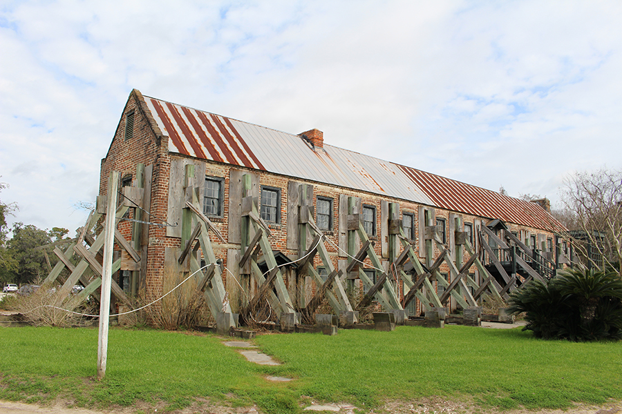 The cotton gin is a long, narrow, two-story brick building upheld by so many wooden beams that it resembles a caterpillar. The natural elements have evidently taken their toll on the metal roof, which is streaked with off-white and rust.