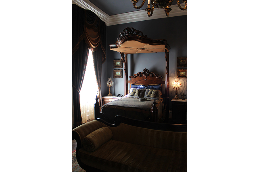 Mrs. Randolph's bedroom is a dark vision of brown and blue. A canopied bed of elegant brown wood rests against a grey wall with blue undertones. It sits behind a pale yellow sofa and is flanked by a pair of lamps dripping in crystal and amber, tiny nautical paintings with frames almost thicker than the actual canvases, and a fleur-de-lis sculpted out of wood.