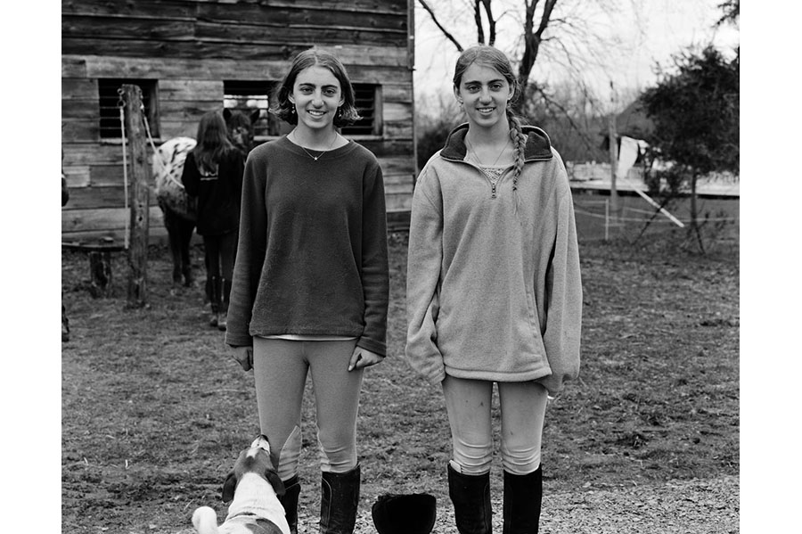 Two young women smiling in front of horse stables (in black and white).