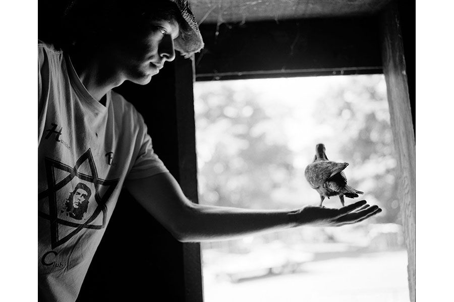 Man holding a bird on the palm of his hand (in black and white).