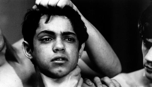 Still from Pier Pasolini's Salò in which a boy's head is held by the hair and neck.