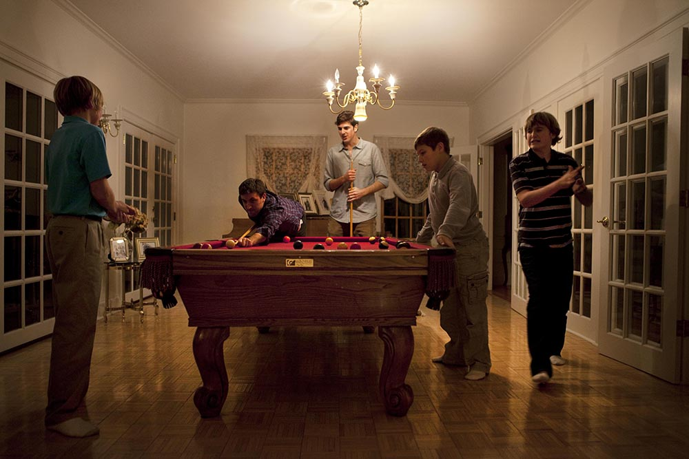 Five boys and men playing pool.