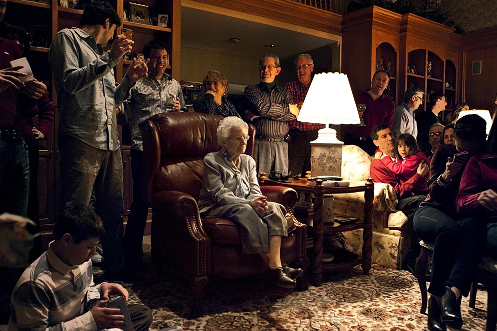 Large family gathered in a living room with a white-haired woman in a leather chair at the center of the frame.
