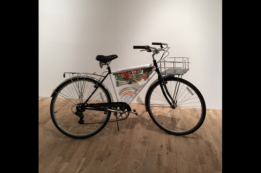 """A plain black bicycle with a triangular poster for """"Flower Facade."""""""