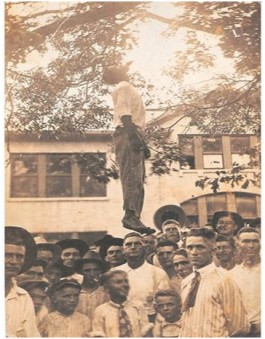 A postcard image with a group of men standing (posing) under a man hanging from a tree.