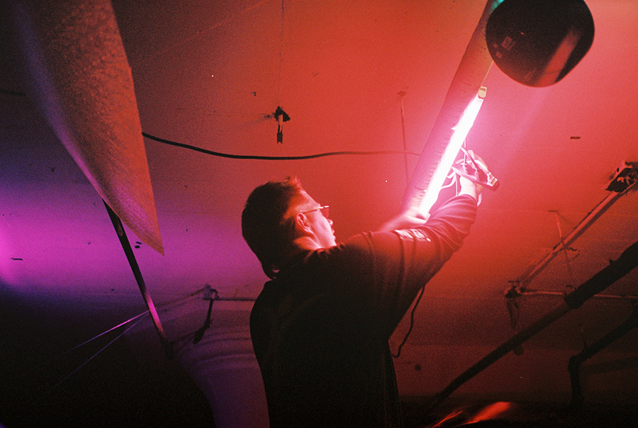 Photograph of a person installing a red tube light, the room awash in a red and pink glow